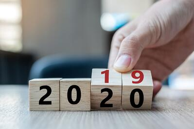 Business man hand holding wooden cube with flip over block 2019 to 2020 word on table background.