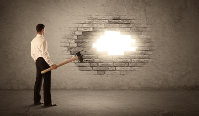 Business man hitting brick grungy wall with hammer and opening a hole.jpeg