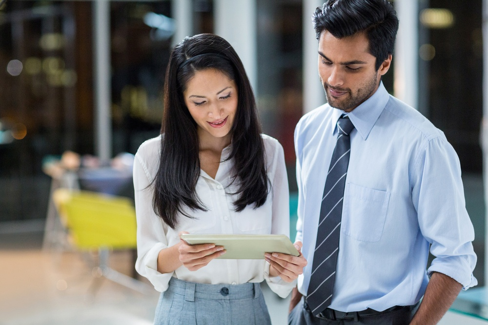 Businesswoman and colleague looking at digital tablet in the office.jpeg
