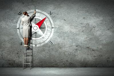 Businesswoman drawing compass with finger on wall standing on ladder-1