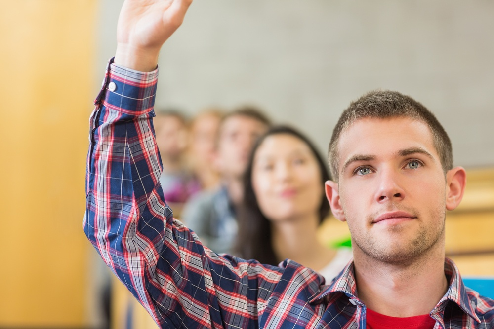 Close-up of a young male student raising hand by others in a row at the classroom.jpeg