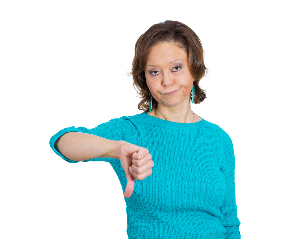 Closeup portrait of unhappy angry mad, pissed off senior mature woman, annoyed, giving thumbs down looking with negative facial expression disapproval, isolated white background. Emotion, sign, symbol