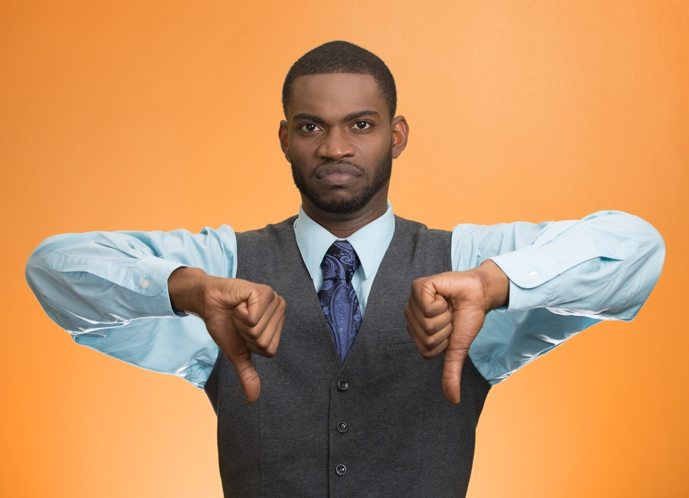 Closeup portrait unhappy, angry, mad, annoyed, grumpy man giving thumbs down gesture, looking with negative facial expression disapproval isolated orange background. Human emotion hand sign, attitude.jpeg