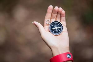 Compass in womans hand in the forest