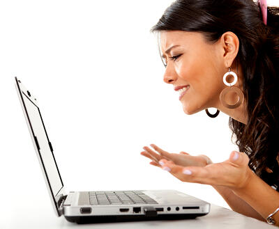Confused woman working on a laptop computer - isolated over white