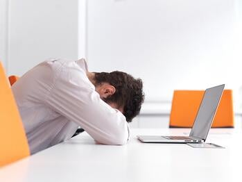 Frustrated young business man have stress problems. Sitting alone at office meeting room  and working on laptop compute..jpeg