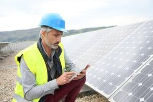 Mature engineer on building roof checking solar panels.jpeg