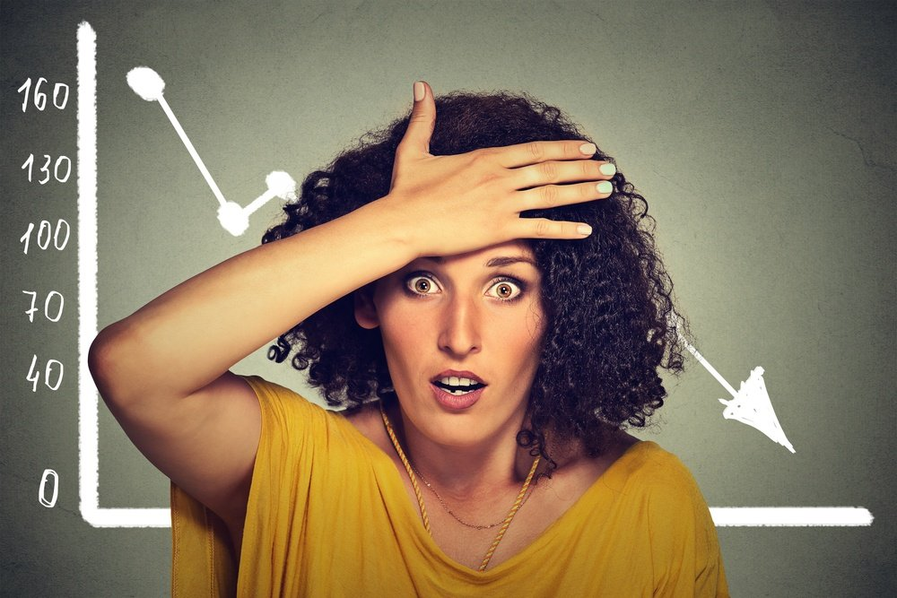 Stressed shocked woman with financial market chart graphic going down on grey office wall background. Poor economy concept. Face expression, emotion, reaction.jpeg