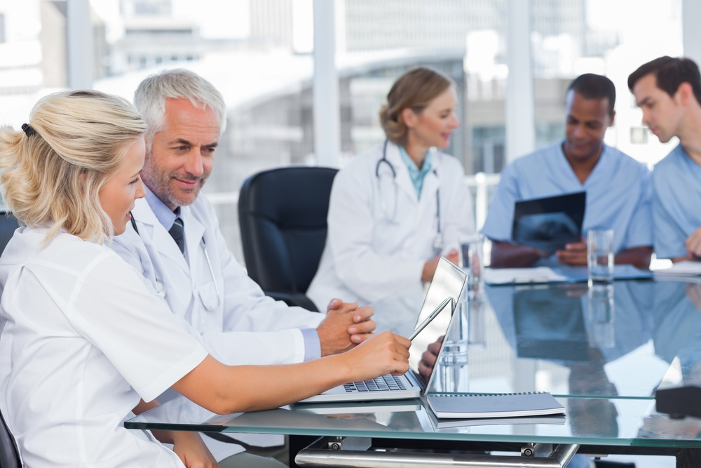 Two smiling doctors using laptop in front of medical team