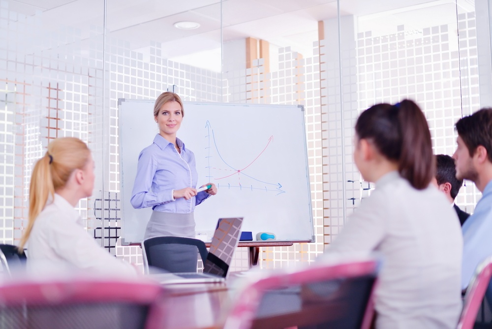 business woman  with her staff,  people group in background at modern bright office indoors.jpeg