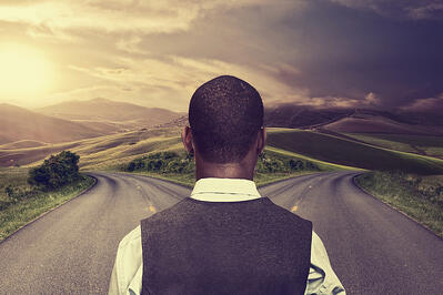 businessman in front of two roads hoping for best taking chance