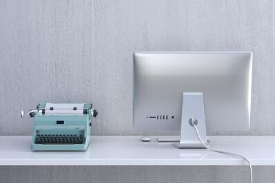 An old fashioned typewriter next to a modern monitor.