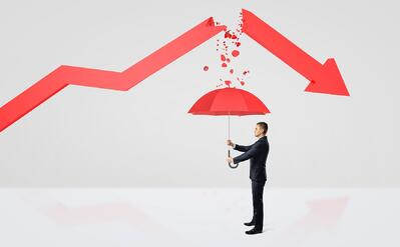 Man with unbrella under a down arrow graph