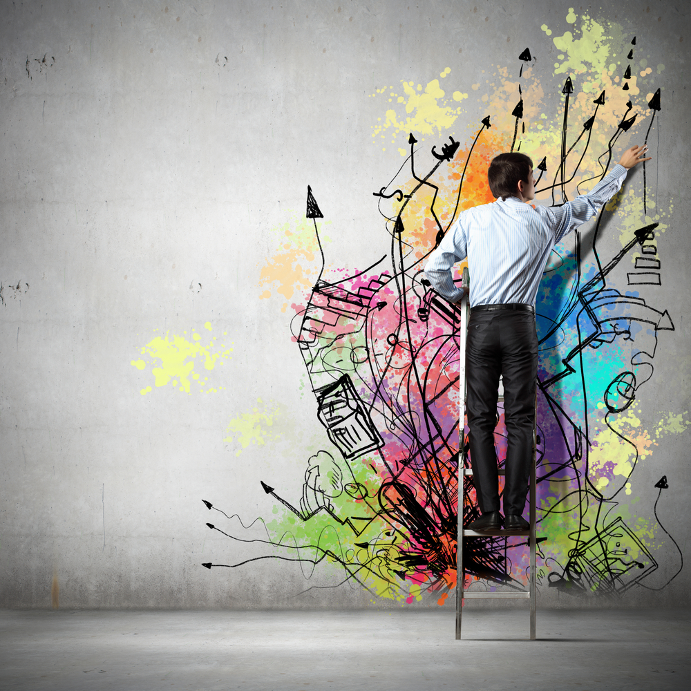 Back view of businessman drawing colorful business ideas on wall