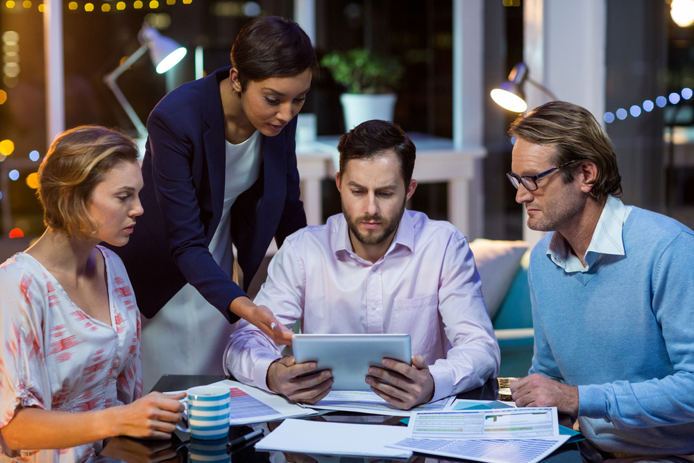 Businesspeople discussing on digital tablet in office at night