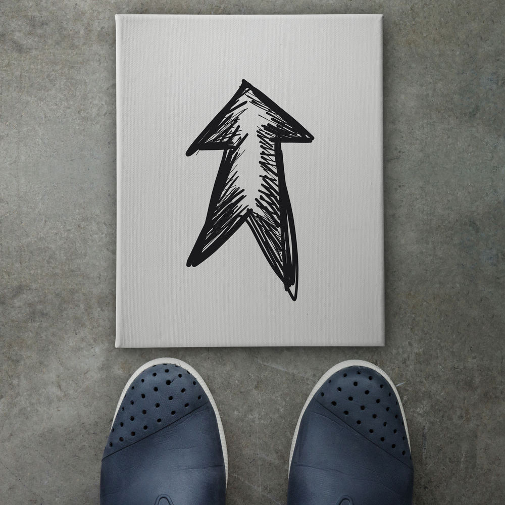 Hand drawn arrow design doodle icon on front of business man feet as concept