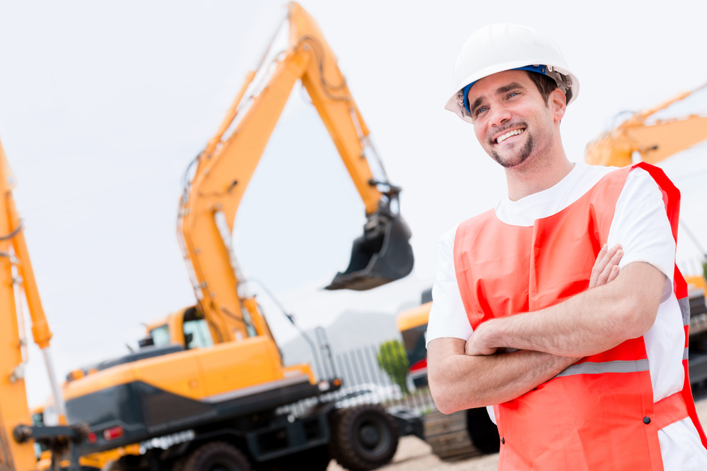 Happy man working with contruction machines and wearing helmet